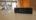 Stacja pomiarowa LIFAair LAM05 na tle pokoju i oczyszczacza LIFAair