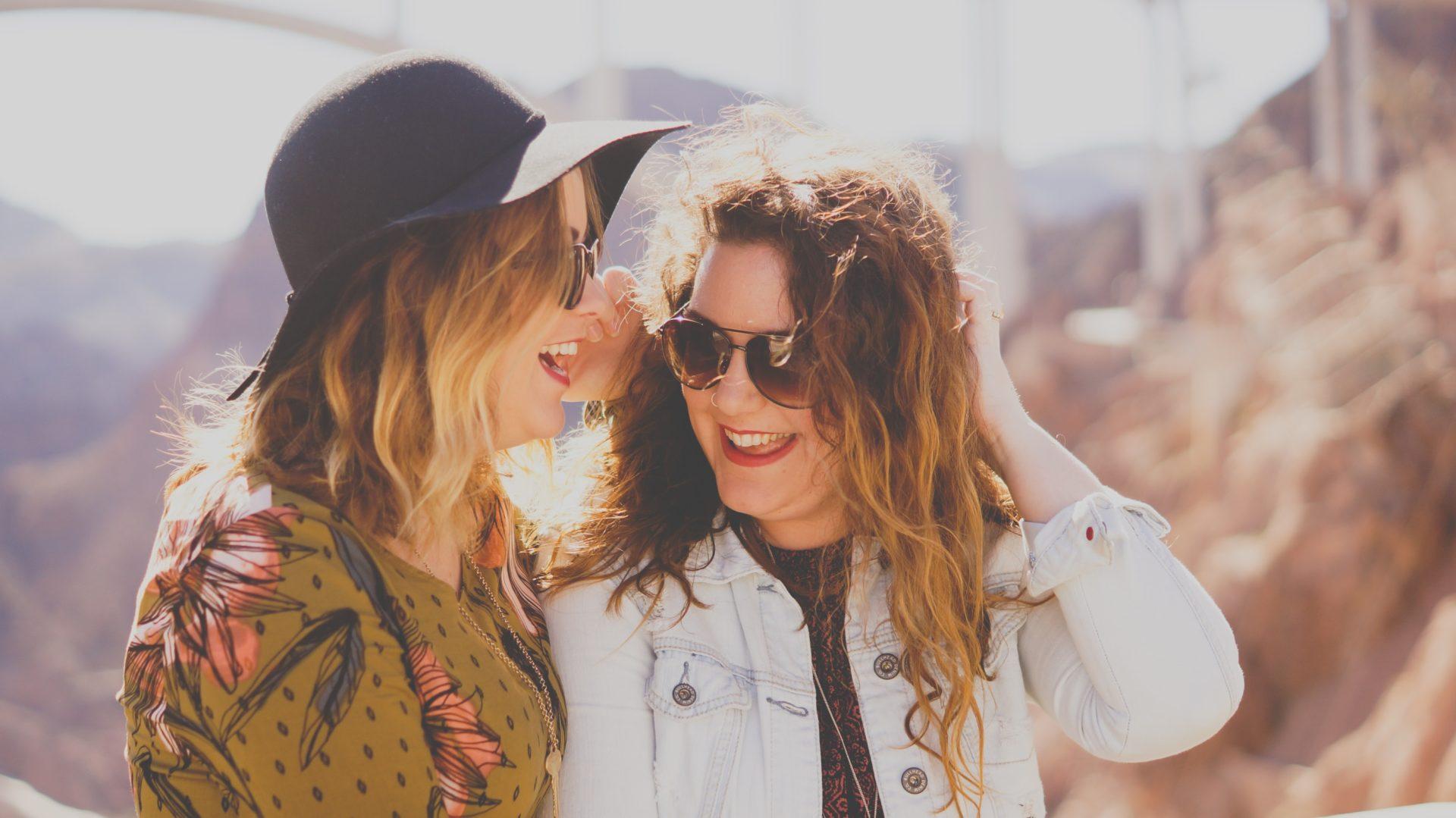 dwie śmiejące się kobiety w okularach słonecznych