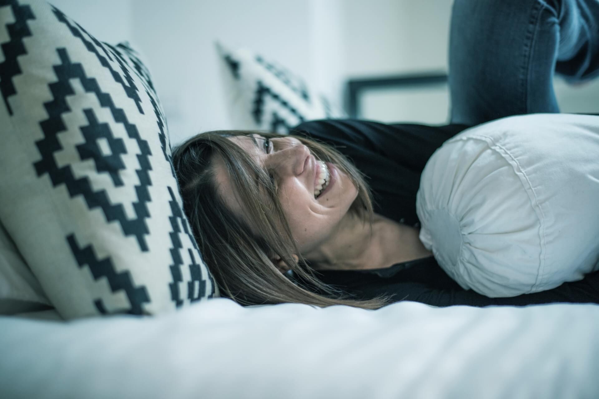 kobieta na łóżku z poduszkami