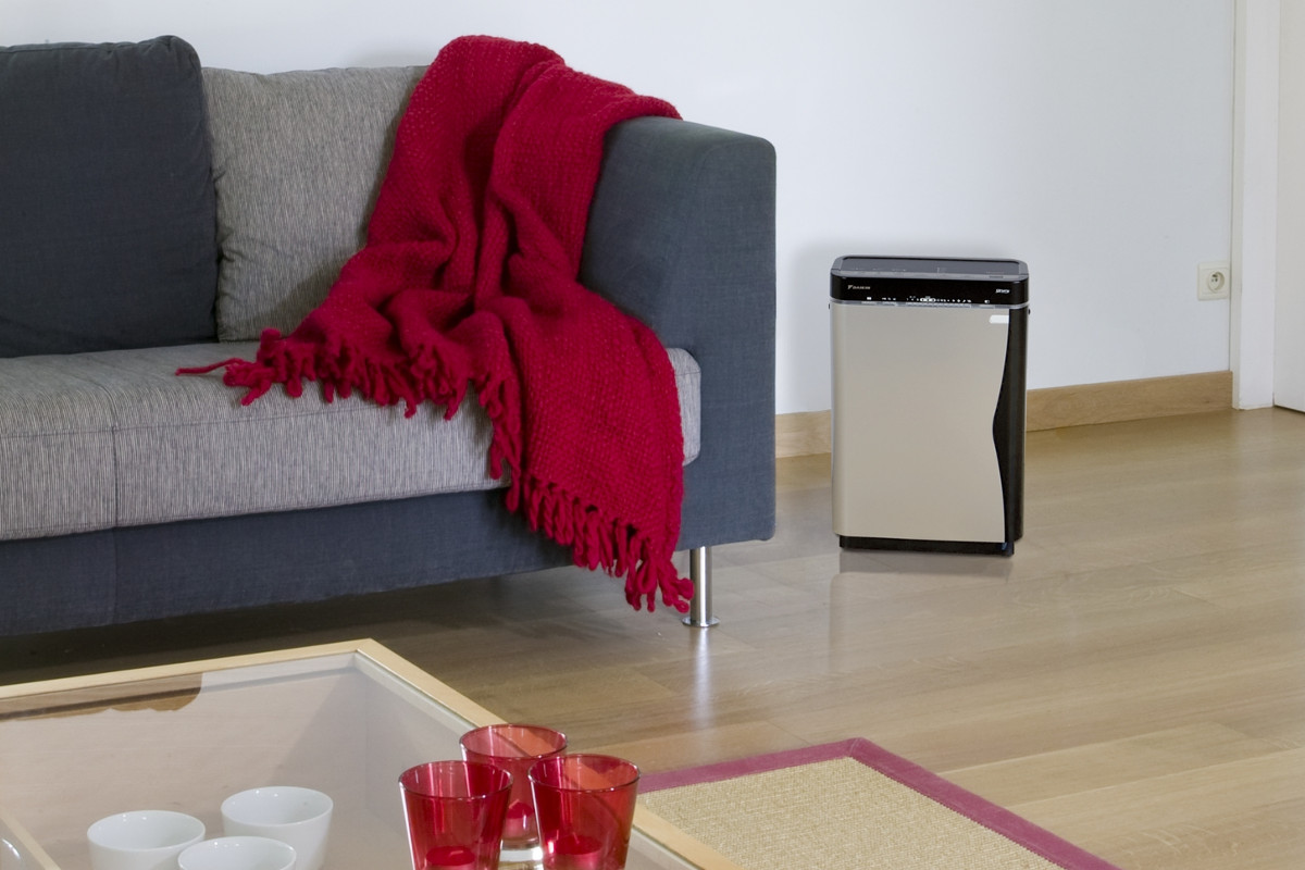 Oczyszczacz powietrza Daikin Ururu MCK75J w pokoju obok kanapy