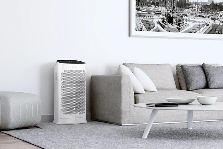 Oczyszczacz powietrza Samsung AX60R5080WD, w pokoju obok kanapy.